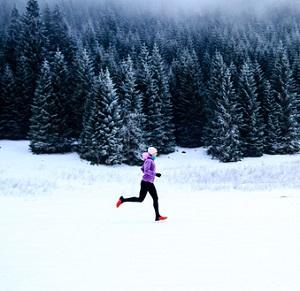 Kvinna som springer i skogen på vintern